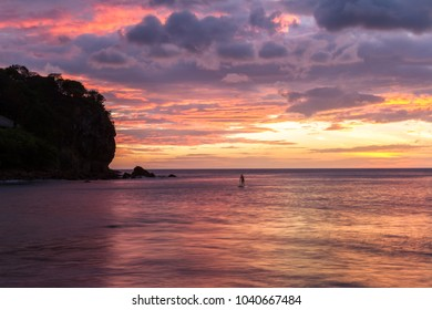 Beautiful sunset at the beach in Nicaragua with a variety of colors reflecting on the wet sand and clouds