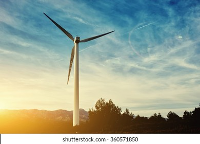Beautiful sunset behind the windmill on the field, electric generator against cloudy sky background with copy space, renewable energy sources, wind turbine location in field