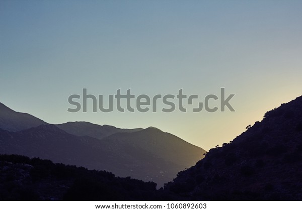 Beautiful sunset, blue sky and dark silhouette of mountains on the island of Crete, Greece