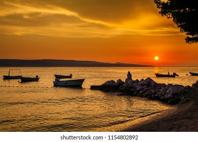 beautiful sunset with the boats and woman sitting on the stones, Croatia