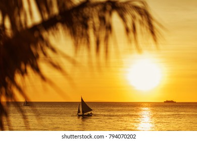 Beautiful sunset at Boracay, Philippines. Sailboats and ship on the sea. Blured palm leaves.