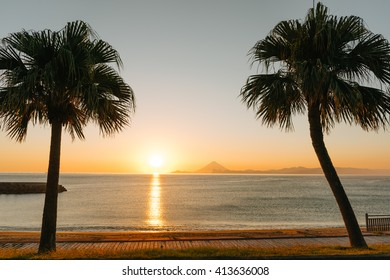 Beautiful sunset by tropical beach surrounded by idyllic palm trees
