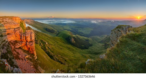 Beautiful sunset in the Caucasus Mountains, view towards Elbrus from the Bermamyt plateau. The setting sun illuminates the rocks.