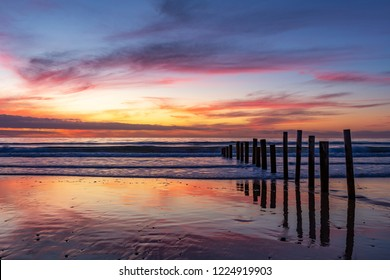 A beautiful sunset with cloud reflections at moana beach with the wooden posts seperating the beach in South Australia on 8th November 2018