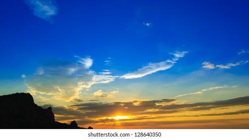 Beautiful Sunset with Clouded Orange Sky and Mountain Silhouette. Crimea, Ukraine