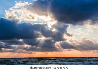 Beautiful sunset in the cloudy sky over the stormy sea