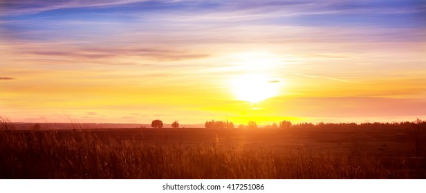 beautiful sunset in cloudy sky over field