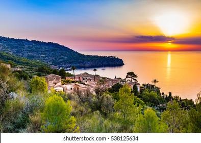 Beautiful sunset at the coast of Majorca Spain island, quaint village at the seaside of Deia, Mediterranean Sea, Balearic islands.