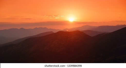 Beautiful sunset colors over the mountains of Peloponnese, Greece. Sun setting after hot summer day.