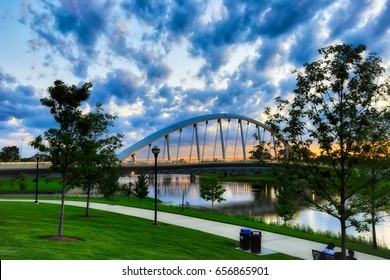 A beautiful sunset in Columbus, Ohio with the Scioto Greenway and the Main Street Bridge in the foreground.
