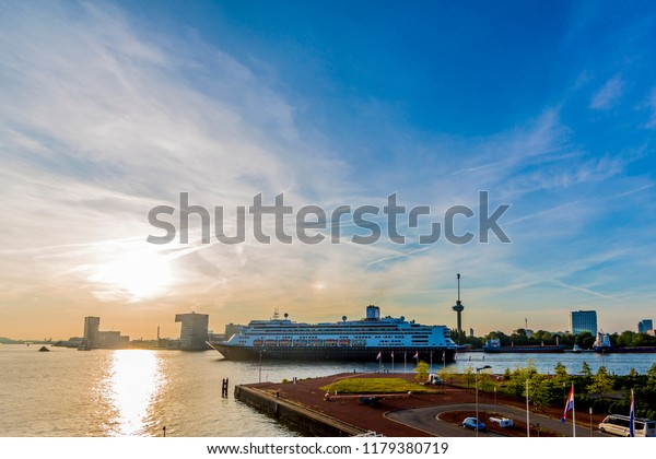beautiful sunset with a cruise ship navigating a canal in the city of Rotterdam in the Netherlands Holland on a beautiful sunny day, copy space
