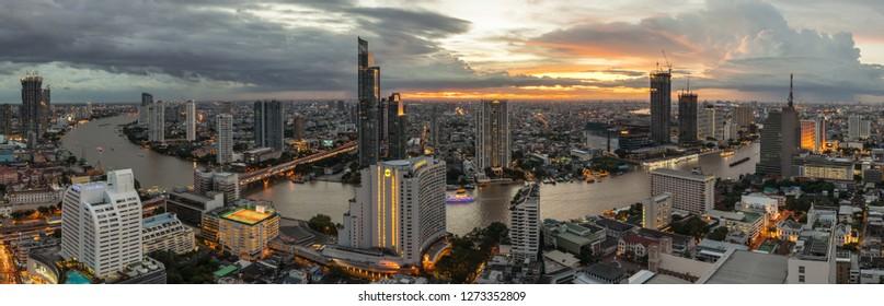 beautiful sunset curve Chao Phraya River panoramic Cityscape of Bangkok city at night on 2018 , panorama the Metropolis Bangkok City downtown urban landscape Thailand