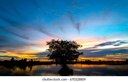 beautiful sunset with dark tree reflection in water,landscape Thailand.sky effect for Long exposure photo taken.