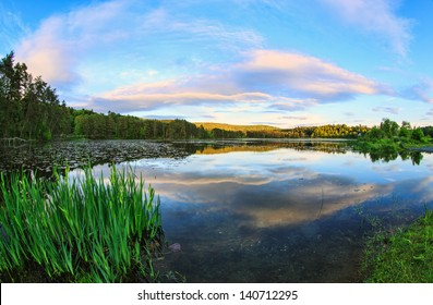 Beautiful sunset at Dewey's Pond in Quechee, Vermont, showing the reflection of the gorgeous sunset sky in the calm waters of this pristine landmark.