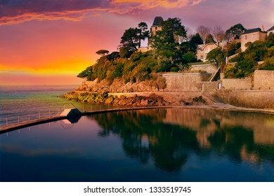 Beautiful sunset in Dinard city, seaside resort in Brittany. View to traditionals houses on cliffs and the artificial pool. France