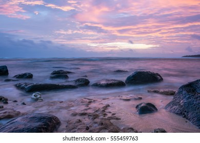 Beautiful Sunset displaying pinks & purples across the clouds, water & rocky beach