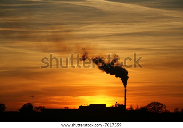 A beautiful sunset and dramatic sky behind a factory with a smoking chimney