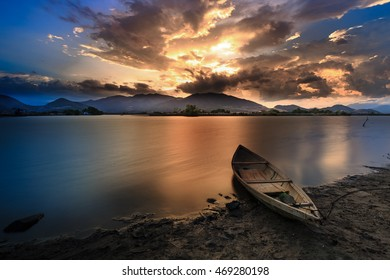 Beautiful sunset with dramatic sky over wild lake and old wooden boat