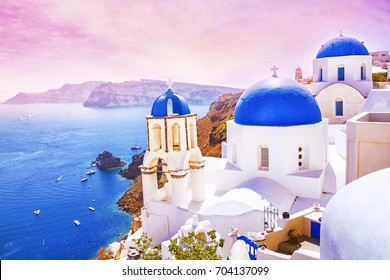 Beautiful sunset in the fabulous village of Oia with traditional white houses and blue domes of the church in Santorini, Greece