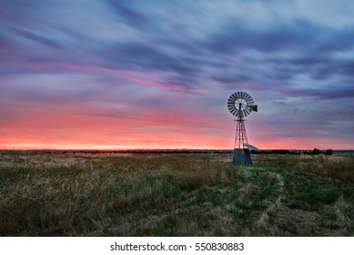 Beautiful sunset falling behind a windmill.