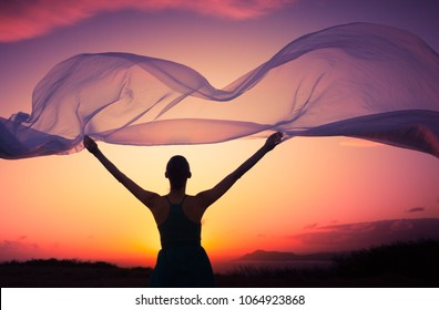 beautiful sunset fantasy girl. Woman holding scarf blowing in the wind.