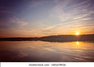 Beautiful sunset in the Finnish archipelago with the sun and clouds reflecting in the water