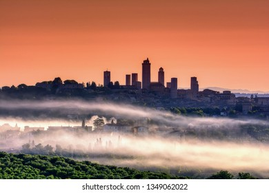 Beautiful sunset with fog at San Gimignano medieval village, Italy.