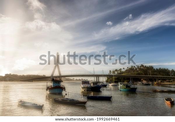 Beautiful Sunset in front of Ilhéus-Pontal Bridge with fishing boats, Ilheus, Bahia, Brazil.
