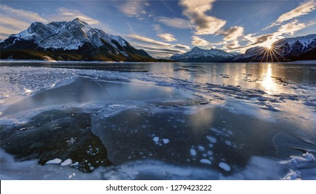 Beautiful sunset at a frozen lake and mountain in Canadian Rockies, Abraham Lake, Clearwater County, AB, Canada