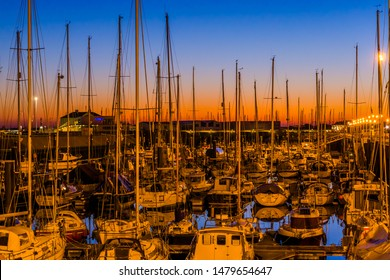 Beautiful sunset in the harbor of blankenberge city, colorful sky with many boats in the water, Belgium, 15 february, 2019