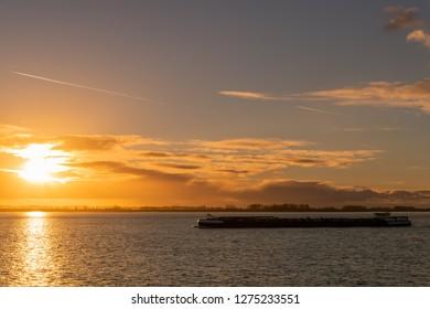 Beautiful sunset with an Inland vessel sailing on the Westerschelde river in the Netherlands. (Translation) binnenvaartschip vaart op de Westerschelde met een mooi zonsondergang.