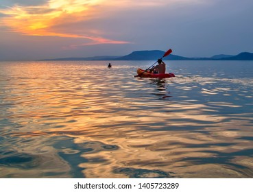 Beautiful sunset at Lake Balaton with a canoeing man and the Badacsony Mountains. Colorful summer background from hungarian sea.