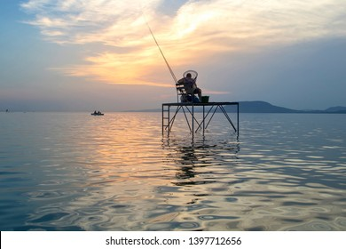 Beautiful sunset at the lake Balaton with  tha Badacsony mountain in Hungary. In the water is a pier with a fisherman fishing.