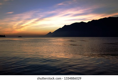 Beautiful sunset at Lake Garda, mountains and cluds can be seen above the lake in the evening