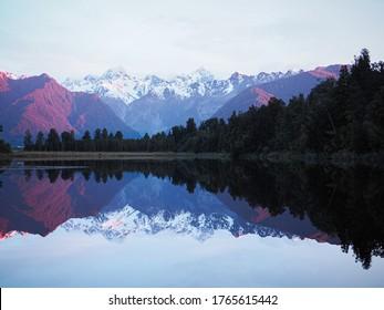 Schöner Sonnenuntergang im Matheson See oder Spiegelsee in Neuseeland, Südinsel. Reflexion des rosafarbenen Schneeberges zum See