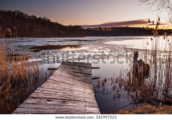 Beautiful sunset landscape with bridge on lake.