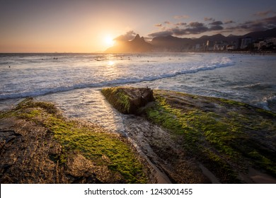 Beautiful sunset landscape by the ocean rocks with mountains on the back, Ipanema Beach, Rio de Janeiro, Brazil