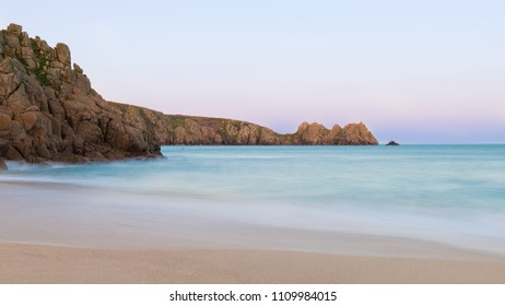 Beautiful sunset landscape image of Porthcurno beach on South Cornwall coast in England