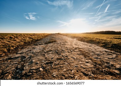 Beautiful sunset landscape on a warm January day in Bavaria, Germany, with a dimishing old concrete road and blue sky in the countryside