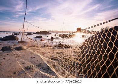 Beautiful sunset landscape with sea beach and fishing net.
