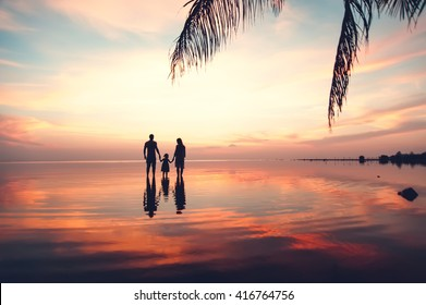 Beautiful sunset landscape with silhouettes of family at the sea