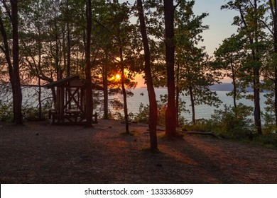 Beautiful sunset landscape with trees and blue sea. Wooden arbor under the oak trees, summer camping area in the evening. Nature background.