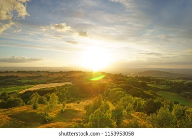 A beautiful sunset, with lens flare, looking towards the Royal Forest of Dean from Painswick Beacon. This is a very popular viewing point in the Cotswolds, Gloucestershire, UK