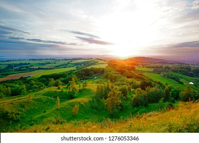 A beautiful sunset, with lens flare, in summer looking towards the Royal Forest of Dean from Painswick Beacon. This is a very popular viewing point in the Cotswolds, Gloucestershire, UK