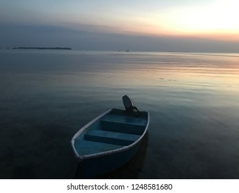 Beautiful sunset with a lonely boat in Karimunjawa Island, Central Java, Indonesia