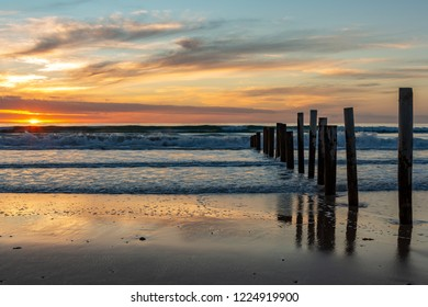 A beautiful sunset at moana beach with the wooden posts seperating the beach in South Australia on 8th November 2018