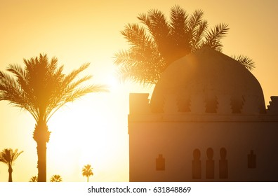 Beautiful sunset moment with Islamic church, palms at background. Silhouette of palm trees with old religious building in Marrakesh town with gold sun rays and lens flare. Wanderlust travel concept.