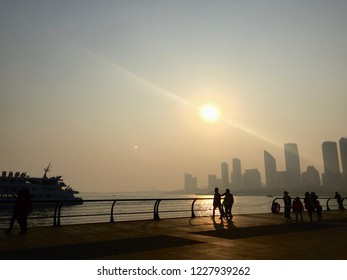 Beautiful sunset with moon in sky and silhouette of people, Qingdao, China.