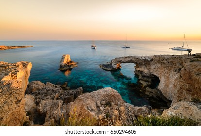 Beautiful sunset at natural stone bridge near Ayia Napa on Cyprus, Europe. Love bridge. Cavo greco