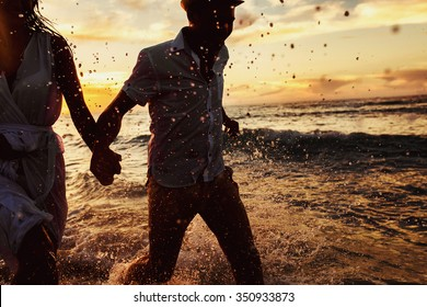 beautiful sunset in the ocean and happy couple running together